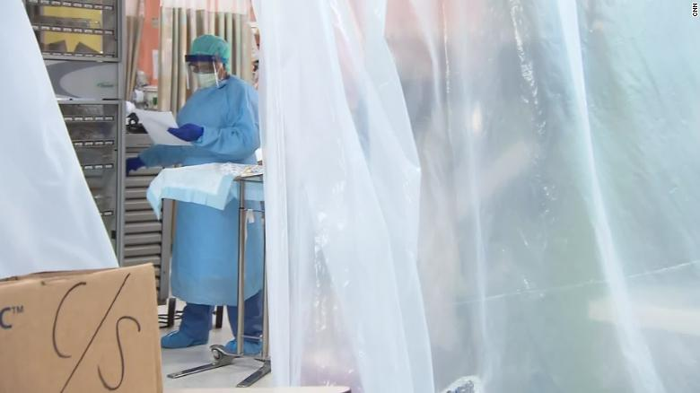 photo of medical worker behind plastic sheet